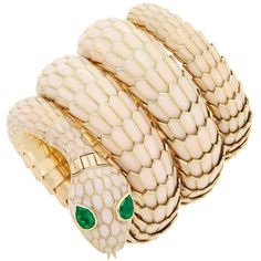 Gold, Enamel and Emerald Snake Bracelet-Watch, Bulgari, Jaeger LeCoultre. 18 kt., the coiled snake's scales applied with pearlescent enamel, outlined in polished gold, its head embellished with 2 pear-shaped emerald eyes.
