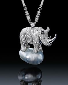 A beautifully rendered African Rhinoceros poses upon a Baroque Pearl in this sparkling, whimsical pendant necklace.