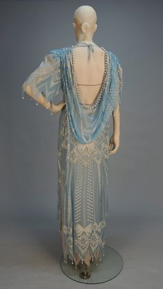 """ZANDRA RHODES HAND PRINTED CHIFFON GOWN, c. 1980. Pale blue with low cowl back, handkerchief pointed short sleeve and hem edged in pearl beads, white printed bow design having rhinestones and sequins at shoulder and back, jersey under dress. Label """"Zandra Rhodes London"""""""