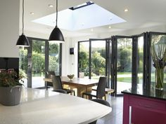 White kitchen with concertina doors to garden Bungalow Extensions, House Extensions, Kitchen Extensions, Porches, Concertina Doors, Glass Extension, Extension Ideas, Rear Extension, Folding Doors