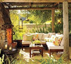terrasse en pierre couverte avec salon de jardin et lanternes suspendues