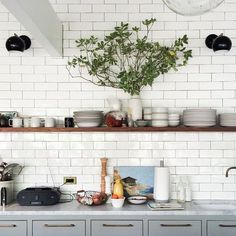 white subway tiles, gray cabinets, brass drawer pulls and open shelves in the kitchen