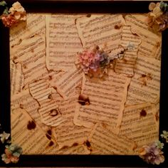 Some old sheet music and some flowers in a picture frame makes a perfect mural above the piano.