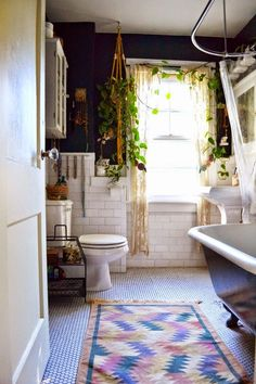 By adding a few live plants & a bright colored, tribal print rug to your bathroom, youve got the perfect Anthropologie-style bathroom design.