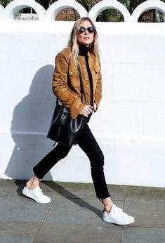 Street style look usando jaqueta de camurça com calça e blusa preto e tênis…
