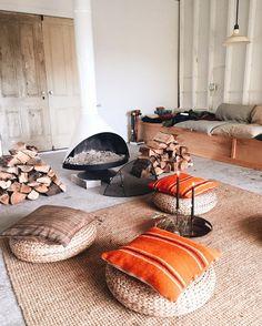 Tapis outdoor en osier, poufs en rotin et coussins orange dans le salon avec cheminée