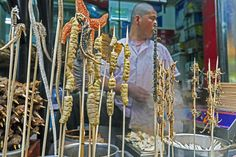 Scorpion on a stick anyone? Yum. Delicacies on skewers for sale at Wangfujing Street night market in Beijing, China.  By travel photographer Gavin Hellier