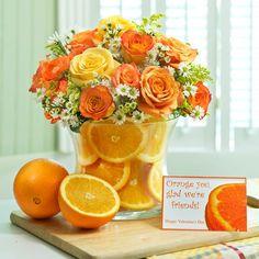 Lindo arranjo de flores e laranjas.