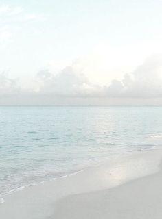 calm. quiet. beach. waves. water. color palette. blue grey white. clouds. sun.