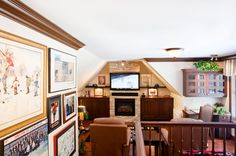 This Realstone Systems man cave has hockey memorabilia, dark wood accents, a real stone fireplace and a pair of chocolate-colored recliners.