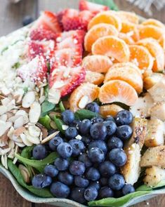 A healthy and incredibly simple spinach salad topped with chicken breast, strawberries, blueberries, toasted almonds, feta cheese, clementin...