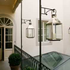 JK Place Florence walkway above dining room silver lantern boxwood planter