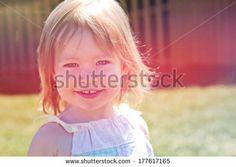 Adorable little girl taken closeup outdoors in summer  by Melissa King, via Shutterstock
