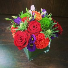 8MT Red Roses, Thistle, Purple Lisianthus, Red Carnations in leaf lined cube vase.