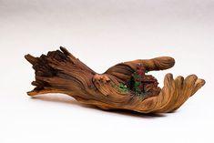 Cette sculpture en céramique (à l'intérieur de la main) impeccablement détaillée appelé Cycles of Decay a été créée par le céramiste Christophe David White qui travaille à Bloomington, dans l'Indiana.  Même si on examine de près les veines du bois avec ses torsions, on ne peut qu'admirer le travail. Tout est magnifiquement sculpté. C'est vraiment magnifique.