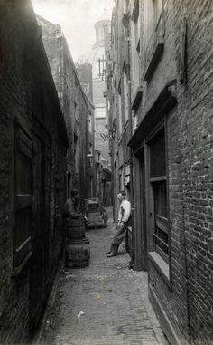 Steden: Klein Hemelrijk ( bij het Kattegat/Singel). Twee mannen staan te praten in deze armoedige steeg in hartje Amsterdam, met de Singelke...
