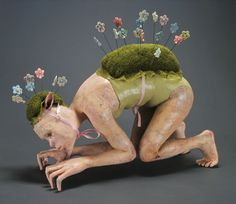 """Artist Magda Gluszek. """"Under Cover."""" terracotta, porcelain, paint, fabric, floral foam, wire, glass eyes. Initially this piece is reminiscent of a feminine version of Golem. But you really have to get up close to this piece and examine it. Magda has this unique style where the faces of her pieces are all very similar looking -- I may even go as far as to say that its the same face in a plethora of expressive expressions. But if you see Magda anywhere near her pieces there's this overwhelming ..."""