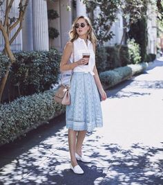 Knot a sleeveless blouse. Wear simple loafers. Skirt comes down just below the knee. Simple purse.
