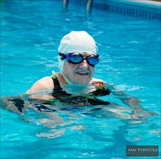 This 95 year old swimming in a swimming pool, wearing a swim cap, goggles and brightly colored bathing suit is a grandmother who leads an active life.    Copyright 2010, Amy Strycula    www.amystrycula.com