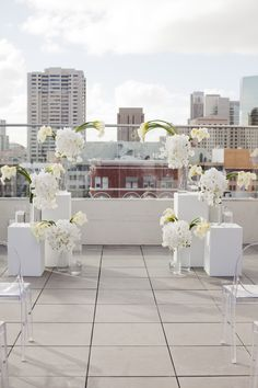 modern ceremony decor with all white flowers and clear ghost chairs