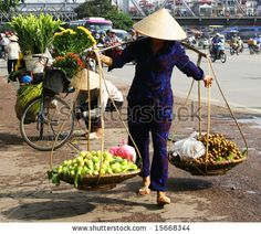 Vietnamese street vendor in Hanoi carrying their produce in baskets suspended on their shoulders