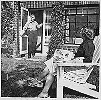 Photograph of Representative Gerald R. Ford Standing in the Doorway of His Apartment at 1521 Mount Eagle Place, Alexandria, Virginia, as Betty Ford Reads a Newspaper in the Yard, 1952