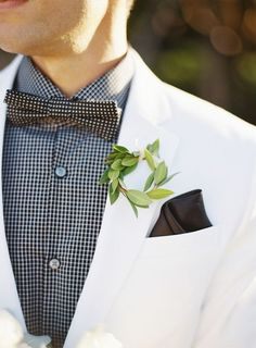 Groom wearing plaid shirt, white tux and polka dot bow tie with a leaf halo boutonniere.