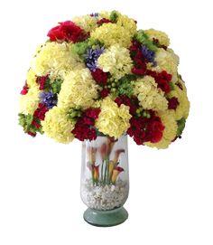 diseño floral redondo con hortensias, agapantos, pinoquios, hypericum y clavel breanthus, sobre base en cristal, decorada con minicalla y pidras decorativas