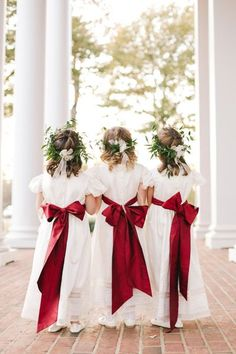 Christmas themed flower girls with white dresses and giant red bows, complete with green hair wreaths.