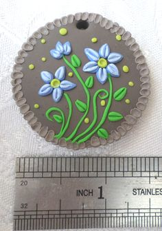 Polymer clay pendant, handmade with applique technique, one of a kind. Light brown, with 2-shaded blue flowers with apple green centers, vibrant green stems and leaves, apple green dots and a light gray-brown frame made of buds. By Lis Shteindel.
