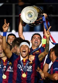 Xavi Hernandez of Barcelona lifts the trophy as he celebrates victory with Neymar after the UEFA Champions League Final between Juventus and FC Barcelona at Olympiastadion on June 6, 2015 in Berlin, Germany.