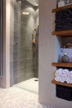 Inloopdouche met glazen deur, pebbles op vloer en houten planken voor de accessoires