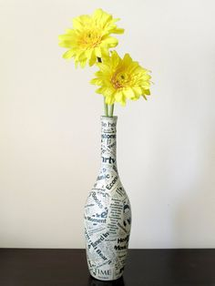 Wine bottles are the perfect shape for a vase if you ask us. Create your own flower holder by covering the bottle in twine, yarn, magazine pages, or other fabric for a standout look.  Source: Etsy User gr3een