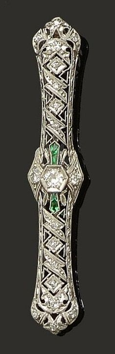 A Belle Époque synthetic emerald and diamond brooch, circa 1915  The pierced lozenge-shaped plaque millegrain set throughout with single and old brilliant-cut diamonds, highlighted with calibré-cut synthetic emeralds, length 6.2cm.