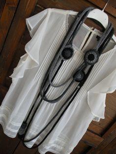 Collana di maglia a più fili nei toni del grigio e nero.