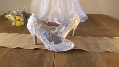 Stunning satin high heel wedding shoes hand decorated with lace, pearls and beads. Finished with a blue ribbon on the buckle to add your