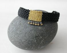 A macrame bracelet with a hematite star bead in purple and gold colors paired wi. Micro Macramé, Macrame Jewelry, Textile Jewelry, Macrame Bracelet Tutorial, Black Gold Jewelry, Minimal Jewelry, Macrame Bracelets, Adjustable Bracelet, Bead Weaving