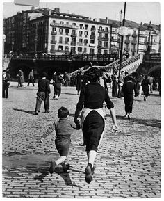Robert Capa, [Woman and child run after an air raid alarm has sounded, Bilbao], 1937