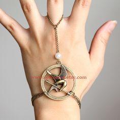 The Hunger Games pendant  Mockingjay Arrow and Peeta pearl bracelet and ring. $6.99, via Etsy.
