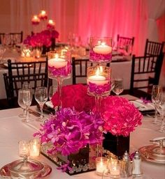 Wedding reception table centerpieces with pink and purple shades of peonies & other flowers and clear glasses filled with water, flowers and floating candles. Beautiful.