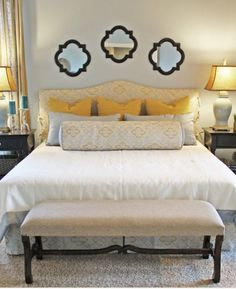 Mirrors above bed, with pops of yellow in the pillows and lamp shades