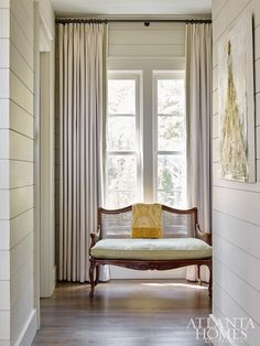 In the master bedroom hallway, a cane-back settee with pretty curves, one of the client's treasured pieces, was updated in a Pindler fabric and Samuel