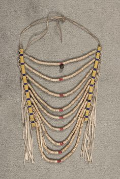 x Nine-strand classic shell necklace accented with red spiny oyster beads and a hawk bell. On fully beaded harness leather. Auction In Santa Fe. Multi Strand Necklace, Tassel Necklace, Crow Indians, Native American Beadwork, Native Style, Chocker, Shell Necklaces, Crows, Leather Working