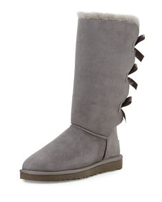 "UGG ""Bailey"" tall sheepskin boot. Dyed lamb shearling (Australia, UK, US, or Ireland) fur lining. 17mm UGGpure 100% wool insole. Flat heel; 1""H. Approx. 11.5""H shaft. Round toe. Fixed satin bows trim"
