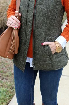 Fall outfit idea with a gorgeous quilted vest, orange sweater and white button up shirt.