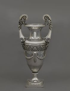 A LARGE SILVER FABERGÉ VASE, IMPERIAL WARRANT, MARK PT FOR IMPORTED GOODS IN CYRILLIC, MOSCOW. Of tapering baluster form with flared neck, gadrooned, upper section flanked by two cast, scroll-end handles with olive sprigs, each handle rising from a cast classical mask, the middle section with collar of cast floral ornamentation above ribbon-tied laurel swags, foot with acanthus border on square socle. Provenance: Family of the Fabergé workmaster, Johan Viktor Aarne, Helsinki.