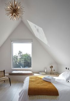 This white modern bedroom has a small window that can be enjoyed when sitting on the built-in bench seating.