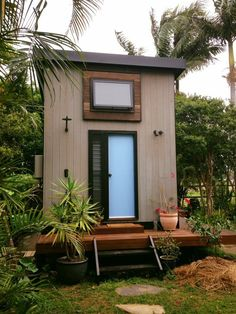Zen tiny house showing our extruded window box and outdoor shower...this is the back door, into the bathroom.