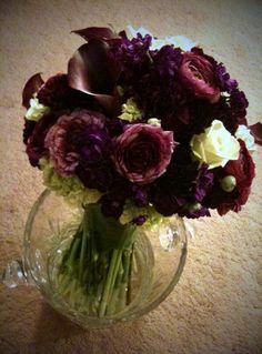 purple ranunculus, deep purple spray stock, mini green hydrangea, black purple carnations, deep purple/wine mini calla lilies, and green roses