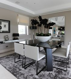 schwarzer Esstisch, weiße Polsterstühle und übergroße Schüssel mit Orchideen